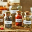 Assortment of spices in glass bottles on cutting board, on wooden background — Stock Photo #72768117