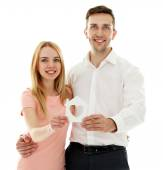 Attractive young couple with decorative house, isolated on white — Stock Photo
