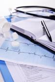 Cardiogram with pills on table, closeup — Stock Photo