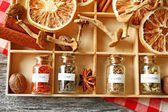 Assortment of spices in glass bottles in box, on wooden background — Stock Photo