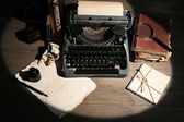 Retro typewriter in lamplight on wooden background — Stock Photo
