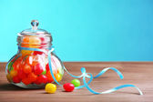 Colorful candies in jar on table on blue background — Stock Photo