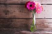 Beautiful bright gerbera flowers in glass vase on wooden background — Stock Photo
