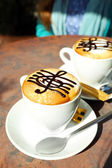 Cups of cappuccino with treble clef on foam on table in cafe — Stock Photo