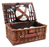 Wicker picnic basket with tableware isolated on white — Stock Photo