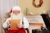 Santa Claus sitting with list of children wishes in comfortable chair near fireplace at home — Stock Photo