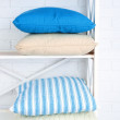 Decorative pillows on shelf on wall background — Stock Photo #72906555