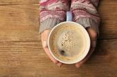 Female hands holding cup of coffee on wooden background — Stock Photo