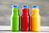 Skleněné láhve čerstvé zdravé šťávy na dřevěné pozadí — Stock fotografie