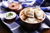 Tasty dumplings with fried onion in brown bowl, on wooden background — Stock Photo