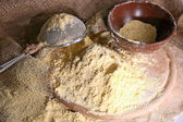 Whole flour with bowl and sieve on wooden cutting board, closeup — Stock Photo