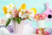 Beautiful flowers in cup, on color wooden background — Stock Photo