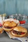Tasty sandwich on cutting board, on color wooden background. Unhealthy food concept — Φωτογραφία Αρχείου