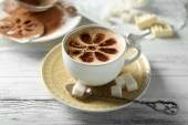 Cup of latte coffee art on wooden table, on light background — Stock Photo