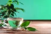 Filiżanka zielonej herbaty na stole na zielonym tle — Zdjęcie stockowe
