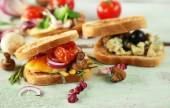 Tasty sandwiches on wooden table, close up — Stock Photo