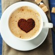 Cup of cappuccino with heart of cocoa on wooden table — Stock Photo #72910753