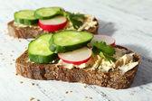 Délicieux sandwichs avec les légumes et le persil sur fond en bois — Photo