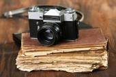 Retro camera with old book on table on green background — Stock Photo