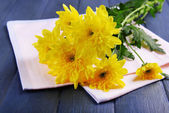Beautiful bouquet of yellow chrysanthemum with napkin on wooden table — Stock Photo