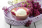 Tasty ice cream and lilac flowers — Stock Photo