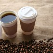 Paper cups of coffee with beans on sackcloth close up — Stock Photo #72965371