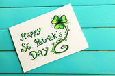 Happy St Patrick's Day card on wooden background — Stock Photo