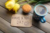 Cup of coffee with fresh cupcake, tulips and Have A Nice Day massage on wooden background — Stok fotoğraf