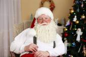 Santa Claus sitting in comfortable chair near fireplace at home — Stock Photo