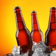 Glass bottles of beer in ice cubes on color background — Stock Photo #73054205