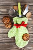 Set of kitchen utensils in mitten with chocolate cookie on wooden planks background — Stock Photo