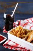 Tasty burger and french fries on plate, on wooden table background. Unhealthy food concept — Φωτογραφία Αρχείου