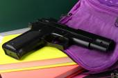 Gun in school backpack close-up, on blackboard background — Stockfoto