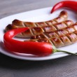 Grilled sausages on plate with chili pepper on table close up — Stock Photo #73088751