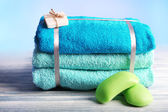 Still life with set of tied towels on wooden surface and light colorful background — Stock Photo