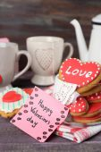 Heart shaped cookies for valentines day, teapot and cups on color wooden background — Stock Photo