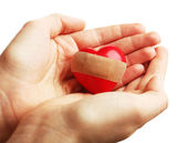 Female hands holding heart with plaster isolated on white — Stock Photo