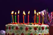 Birthday cake with candles on purple background — Stock Photo