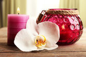 Spa still life with candle and white orchid flower on wooden table on light background — Stock Photo