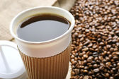 Paper cup of coffee with beans — Stock Photo