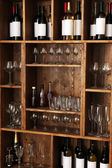 Shelving with wine bottles with glasses — Stock Photo