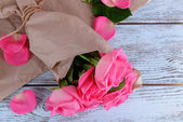 Beautiful pink roses on wooden table with parchment, closeup — Stock Photo