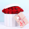 Bouquet of red roses in textile box with present on wooden background — Stock Photo #73478625