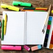 Notebook and bright school stationery on old wooden table — Stock Photo #73478737