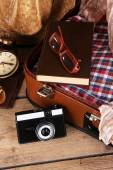 Packing suitcase for trip on wooden background — Stock Photo