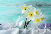 Fresh narcissus flowers in tray with fabric on wooden background — Stock Photo