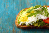 Tasty sandwich with egg, avocado and vegetables on wooden background — Stock Photo