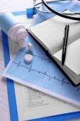 Eletrocardiograma com comprimidos na mesa, closeup — Fotografia Stock