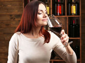 Young woman tasting wine in cellar — Stock Photo