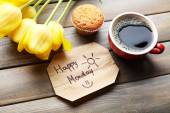 Cup of coffee with fresh cupcake, tulips and Happy Monday massage on wooden background — Stock Photo